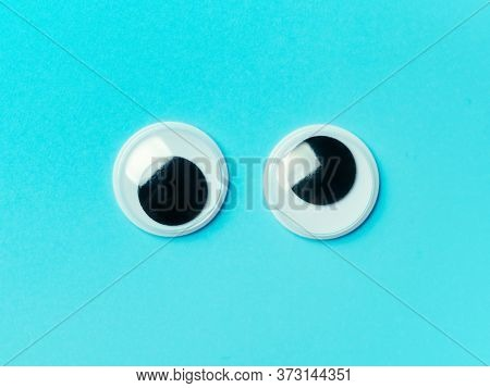 Googly Eyes On Blue Background. Top View Or Flat Lay. Plastic Toy Eyes On Turquoise Background