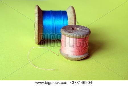 Cotton Thread Reels Bobbin Pink And Blue On Bright Background With Copy Space