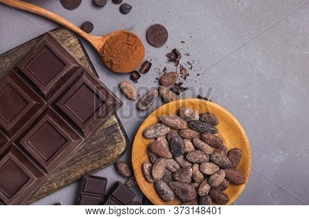 Chocolate Bar And Drops, Cocoa Beans And Powder On Grey Background