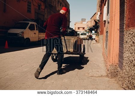 Tired Porter Man With Heavy Trolley And Tourist Luggage Walking At Street To Hotel In Marrakesh, Mor