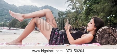 Casual Girl Using Mobile Phone And Lie On Beach Sand