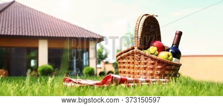 Picnic Basket With Fruits, Bottle Of Wine And Checkered Blanket On Green Grass In Garden, Space For