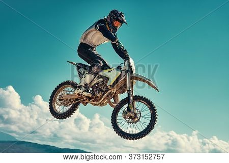 Racer On Mountain Bike Participates In Motocross Race, Takes Off And Jumps On Springboard, Against T
