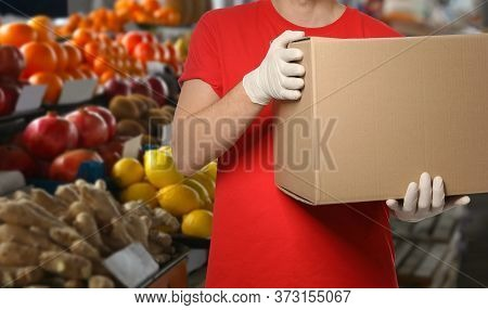Man With Cardboard Box Against Fresh Fruits In Store, Closeup. Wholesale Market