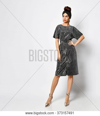 Gorgeous Young Woman With Combed Hair Posing In A Stylish Bandage On Her Head And A Shiny Coal Dress