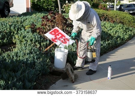 Lake Forest, CA / USA - June 23, 2020: A Bee Remover wearing coveralls, face mask, Bee Head, Face Cover and Gloves, removes and sprays a Water Meter to remove and eradicate a hive of Killer Bees.