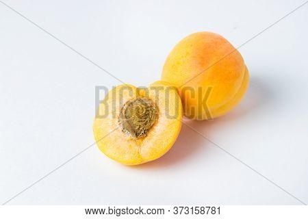 Apricots On A White Background. Half An Apricot With A Stone And A Whole Apricot Next To It