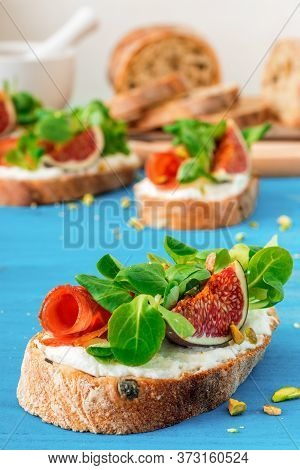 Toast From Swiss Twisted Bread, With Feta Cheese Or Ricotta, Fresh Figs, Rolled Slice Of Bacon, Fres