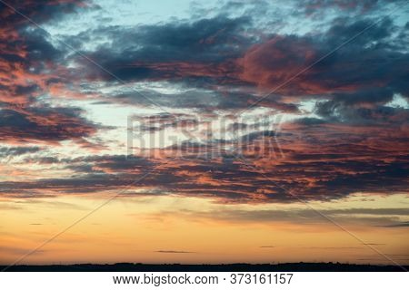 The Sky At Sunset Is Orange And Red With Clouds, The Sky Is Dramatic Colors