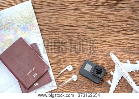 Passport With A Map On Old Wooden Background.travel Planning.top View Of Traveler Accessories With A