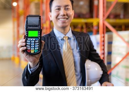 Portrait of businessman hold credit card reader in large factory and distribution warehouse environment. Business deal merger acquisitions and takeover.