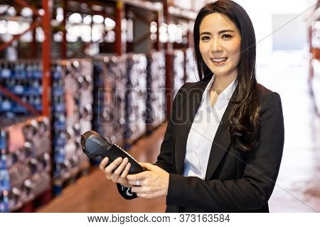 Portrait of businesswoman hold credit card reader in large factory and distribution warehouse environment. Business deal merger acquisitions and takeover.