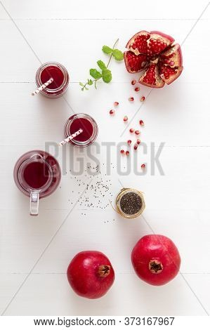 Pomegranates And Chia Seeds With Fresh Mint. A Glass Pitcher Of Fresh Red Juice With Two Full Jars.