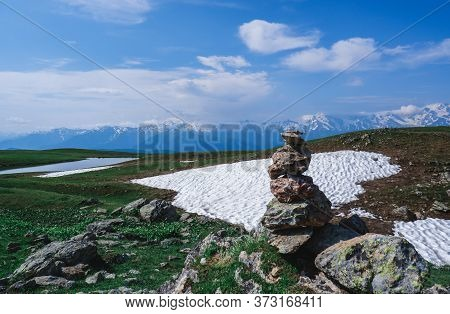 Balancing Stones. Balance Of Stones On The Background Of Snow In The Mountains. The Mountains Of The