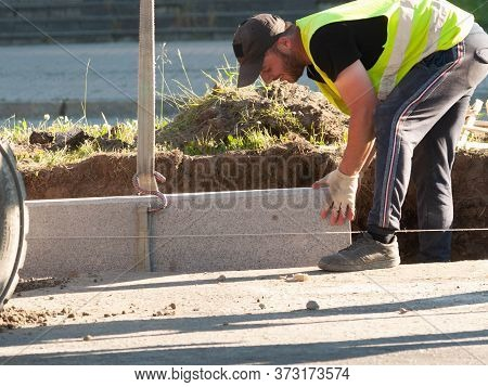 A Smiling Road Worker During The Installation Of A Road Curb