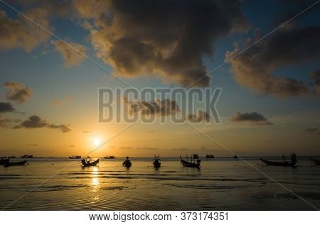 Beautiful sunset on tropical island, Koh Tao, Thailand. Boats in low tide water, yellow clouds