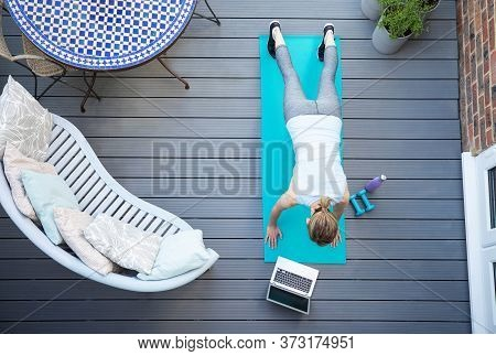 Overhead View Of Healthy Mature Woman Following Online Exercise Class On Laptop At Home On Deck