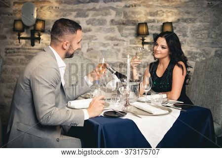 Romance and dating concept. Young couple man and woman with champagne glasses celebrating and toasting in restaurant. Two people male and female in elegant evening suit and dress on romantic dinner.