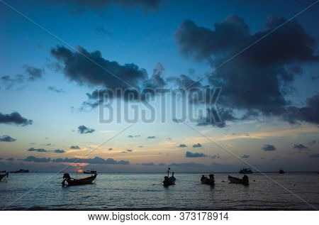 Beautiful sunset on tropical island, Koh Tao, Thailand. Boats in blue water
