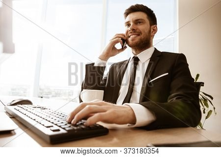 Business concept. Young businessman sitting at the office table happy talking on a cell phone getting good news about his work. Hands on keyboard. Man in suit indoors on glass window background.