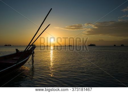 Beautiful sunset on tropical island Koh Tao, Thailand. Boat in water and last sun