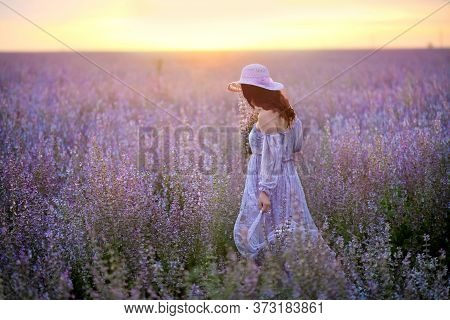 A Young Lady With Red Hair In Purple Dress And Pink Hat Walking Through The Sage Colorful Field With