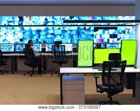 interior of big modern security system control room with blank green screens, workstation with multiple displays, monitoring room with at security data center  Empty office, desk, and chairs at a main