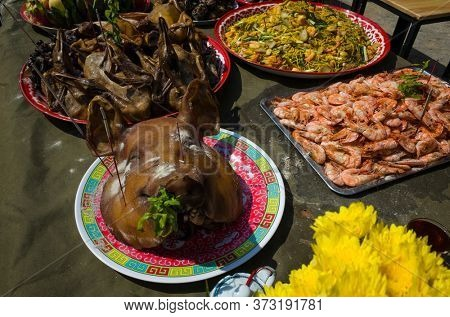 Big cooked pig head on plate on table among other dishes offerings to God at Chinese New Year in Koh Tao island, Thailand