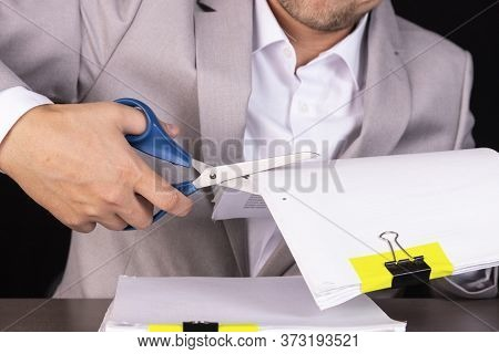 Concept Of Mergers And Acquisitions In Business. A Businessman Cuts A Stack Of Papers With Scissors.