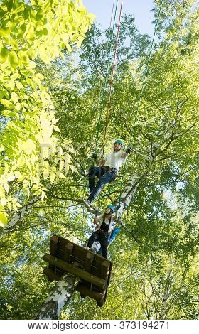 Rope Adventure - Woman And Man Having A Rope Entertainment In The Green Forest - Standing On High An