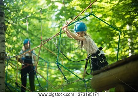 Rope Adventure - A Little Girl Walks On The Rope Bridge To The Stand And Holding By The Ropes With H