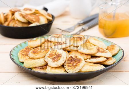 Trend Breakfast. Dutch Mini Pancakes On A Plate And A Frying Pan With Them On A Wooden Table. Close-