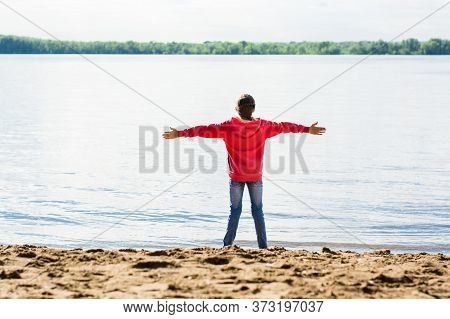 Local Travel. Girl On The Bank Of The River In The Sand With Outstretched Arms. Summer Tourism