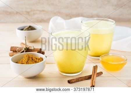 Detox Drink. Golden Milk With Turmeric And Cinnamon In Glasses On A Wooden Table.