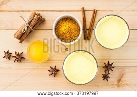 Detox Drink. Golden Milk With Turmeric And Cinnamon In Glasses And Ingredients For Cooking On A Wood