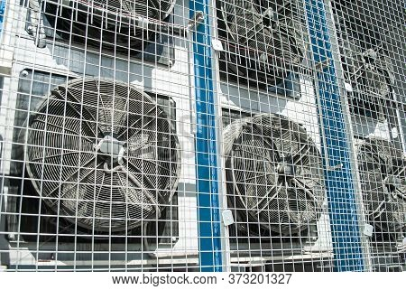 Close Up Of Large Industrial Air Conditioning Fans Behind A  Protective Gratings. Fans Are Running.