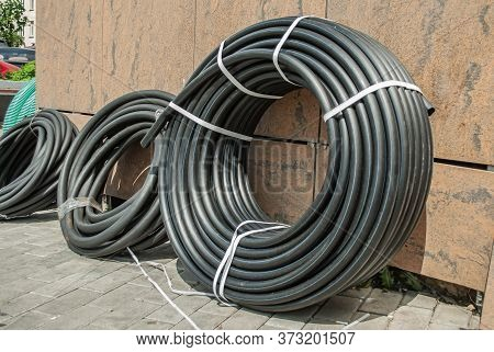 A Rolled Up Black Industrial Rubber Hose Tied With Rope On The Street. Products For Irrigation Syste
