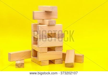Tower Of Wooden Blocks On Yellow Background With A Copy Of The Space. Concept Of Building Business O