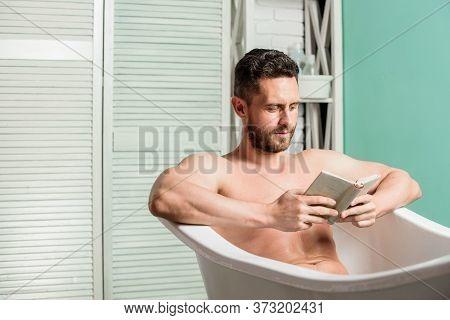 Macho Enjoying Book In Bath. Sexy Man In Bathroom Reading. Macho Naked In Bathtub. Sex And Relaxatio