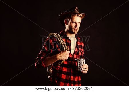 Sheriff Concept. Brutal Cowboy Drinking Alcohol. Western Culture. Man Wearing Hat Hold Rope And Flas