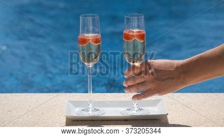 Woman Takes A Glass With Champagne Or Prosecco With Raspberry On Swimming Pool Or Sea Blurred Backgr
