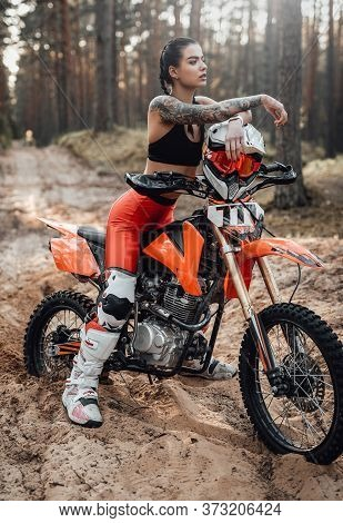 Beautiful Female Racer Wearing Motocross Outfit With Semi Naked Torso Sitting On Her Bike In The For