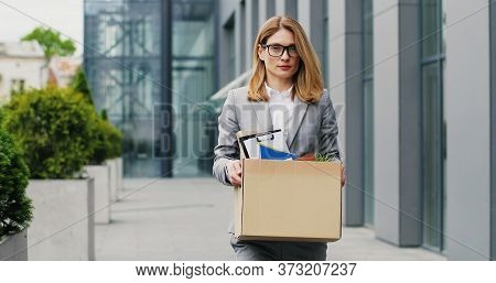 Caucasian Female Office Worker Holding Box Of Personal Stuff And Walking The Street. Businesswoman L