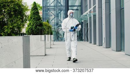 Man In White Suit, Goggles, Gloves And Respirator Walking Street In City. Male Healthcare Worker Of
