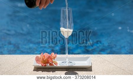Waiter Pours Champagne Into A Glass With Bubbles And Foam On Swimming Pool Or Sea Blurred Background