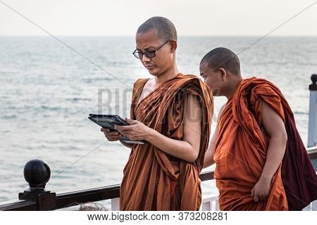 Colombo, Sri Lanka - February 19, 2019: A Buddhist Monk With Orange Clothes Looking His Tablet At Th
