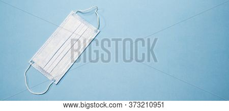 Disposable Medical Mask On Blue Background. Protective Face Mask From Coronavirus. Surgical Cotton M