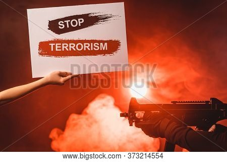 Cropped View Of Woman Holding Card With Stop Terrorism Lettering Near Man Holding Machine Gun On Bla
