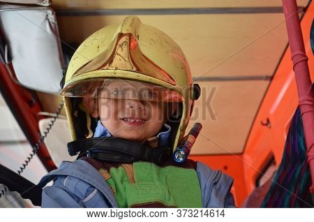 Little Boy Acting Like A Fireman. Boy Sitting In A Real Fireman Car. Dreaming Of Future Profession.