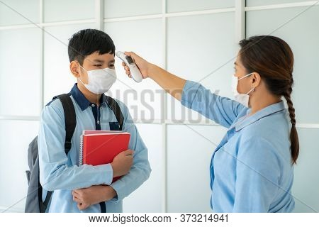 Asian Woman Teacher Using Thermometer Temperature Screening Student For Fever Against The Spread Of